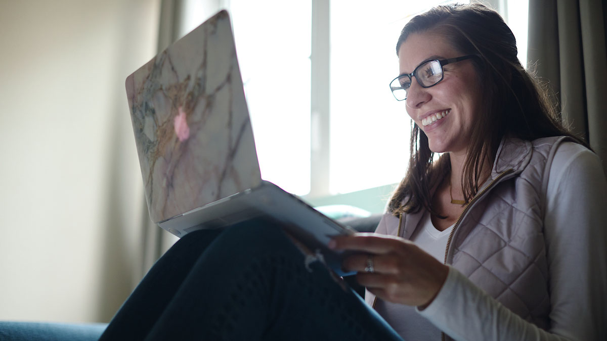 Picture of smiling student sitting on bed with laptop